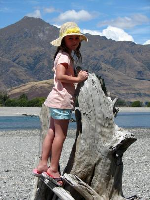 Stella Ross enjoys the view from a  piece of driftwood while on holiday at Lake Wanaka on January...