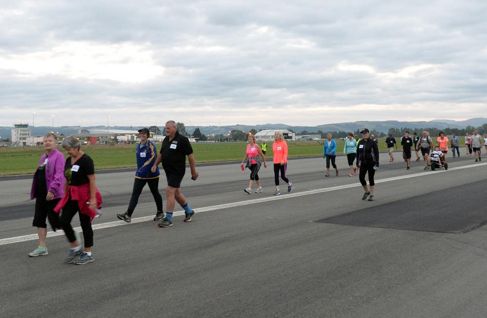 Some of the 120 walkers and runners to enter the first Run the Runway event make their way down...