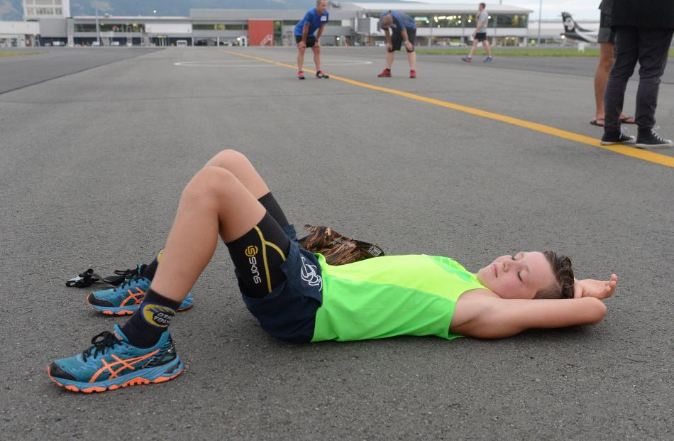 Nick Casey (12) rests on the tarmac after finishing the run in a time of 19 minutes and 59 seconds.