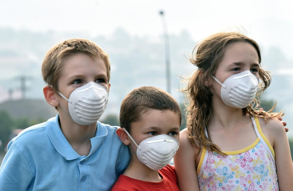 Tyler Drew (10, left), Logan Williamson (7) and Izabelle Williamson (10) in Clermiston Ave protect themselves from the smoke.