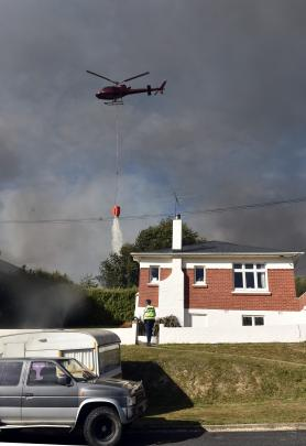 A helicopter puts out a fire on a Mulford St property.