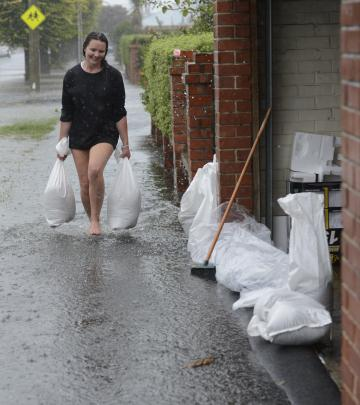 Shannon Goodwin helps sandbag her neighbour's property in Surrey St. Photo: Gerard O'Brien
