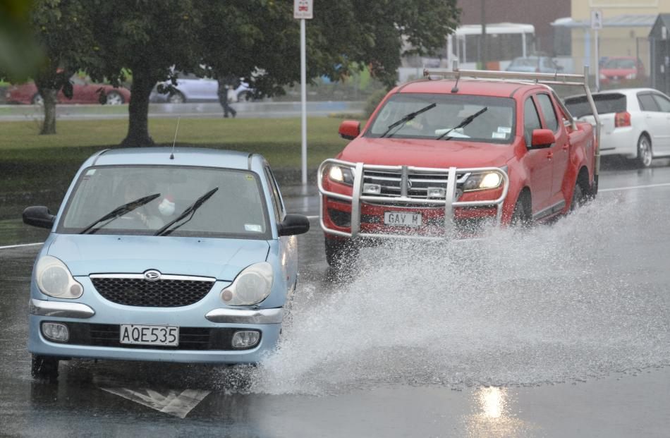 Motorists drive through a pool of water at the intersection of Andersons Bay Rd and Crawford St....