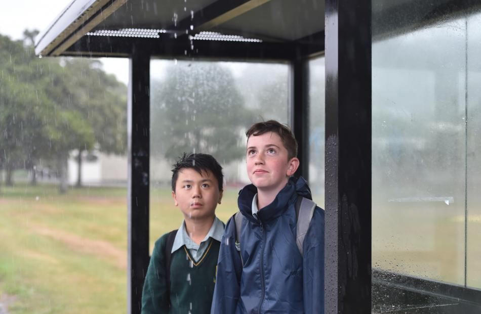 Andrew Hua (12, left) and Kyall McKean (13) wait for a bus after Bayfield High School was closed....
