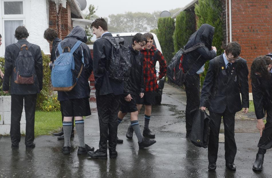 Drenched King's High School pupils wait for a bus in the rain in Bay View Rd. Photo: Gerard O'Brien