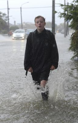 King's High pupil Henri Houliston-Hockney trudges home through floodwater in Forbury Rd. Photo:...