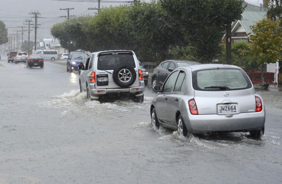 Traffic eases through a flooded Surrey St. Photo: Gerard O'Brien