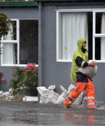 Firefighters place sandbags  around Radius Fulton Rest-Home yesterday. Photo: Peter McIntosh