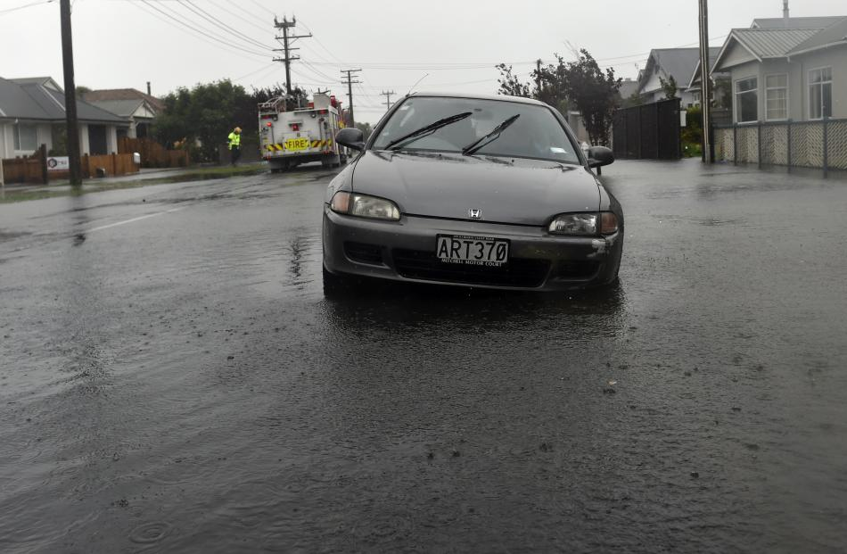 A vehicle drives through flood water in St Clair. Photo: Peter McIntosh