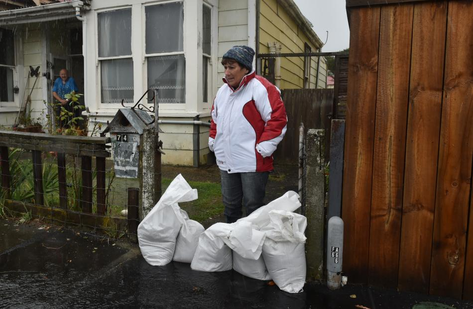 South Dunedin resident Leona Hurndell stands behind sandbags which she hopes will halt floodwater...