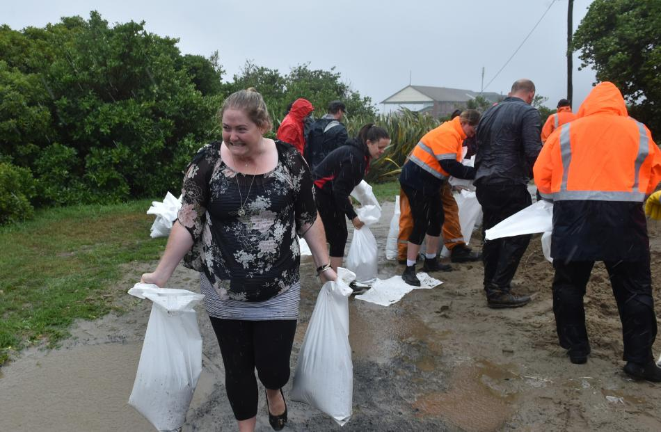 Joanna Bishop-Cherry, of South Dunedin, carries sandbags back to her car at the St Clair Tennis...