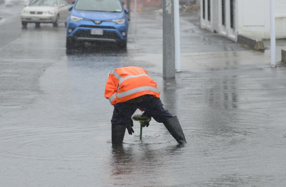 A contractor clears a blocked sump in Andersons Bay Rd yesterday morning. Photo: Gerard O'Brien