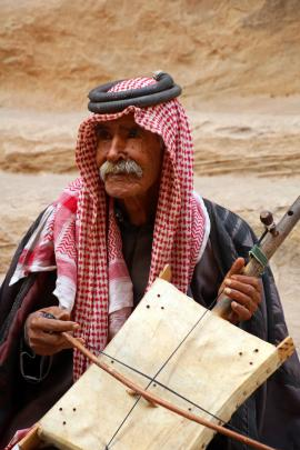 A Bedouin musician plays a rababa, a traditional instrument that is an Arab fiddle.