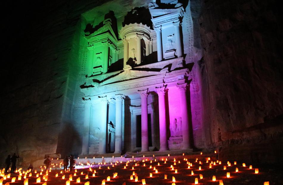 Coloured lights and candles illuminate the Treasury building during the thrice-weekly ceremony, '...