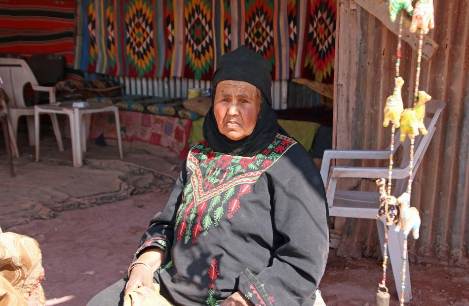 A Bedouin woman in her souvenir stall along a mountain path in Petra.