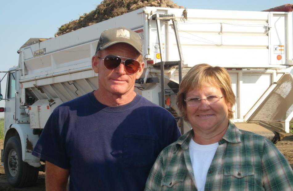 John and Meredith McLeod cover up during their potato harvest due to the sun and heat. The temperature tops 30degC every day in summer and sometimes hits 40degC. The leaf material among the potatoes on the truck behind them has to be removed by hand. Phot