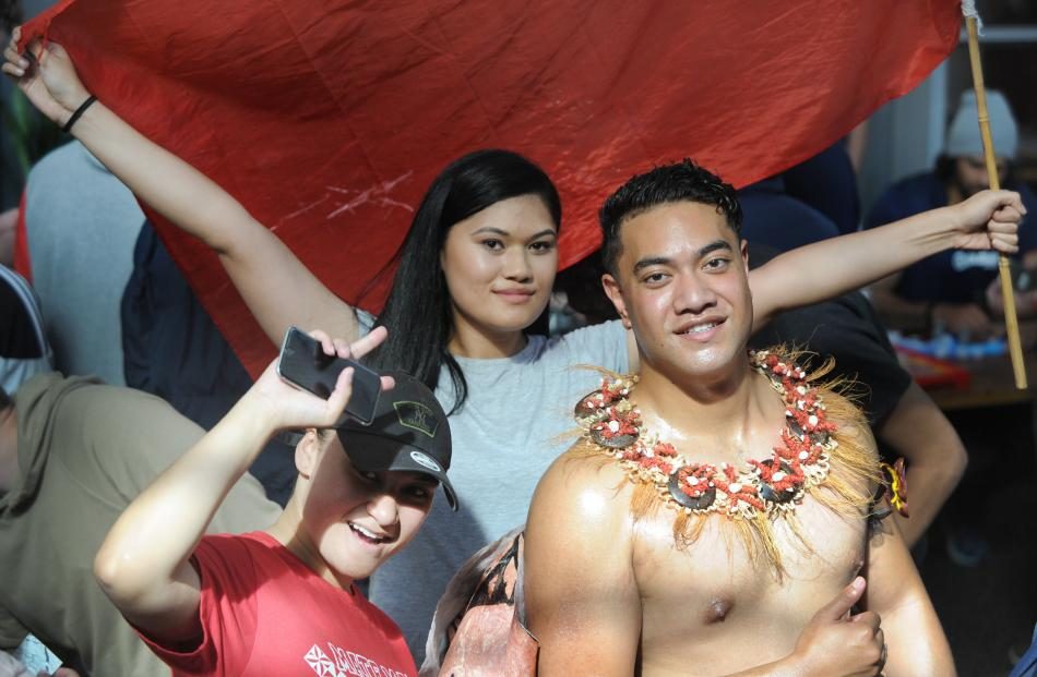 (L-R) Alisi Kivalu, Peresi Sita (holding flag), and Isileli Veikoso of The Tongan Students'...