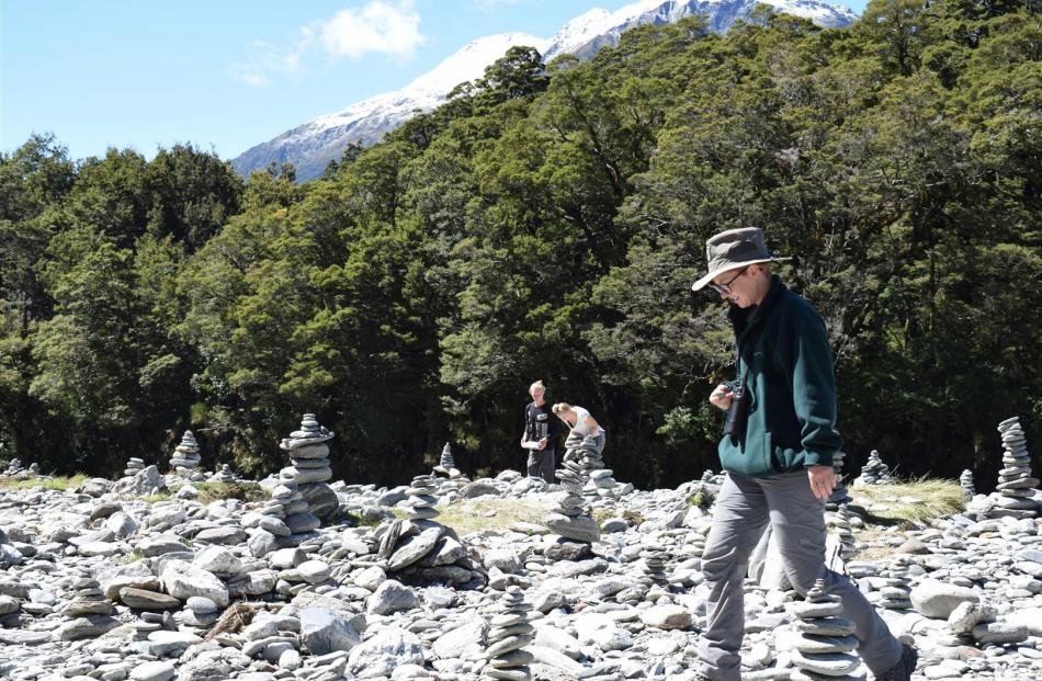 Doc ranger Sophie Briggs walks past Jonatan Johansson and Sara Klint (both 20), of Sweden, trying rock stacking for the first time and adding their stack to the many beside the Blue Pools.