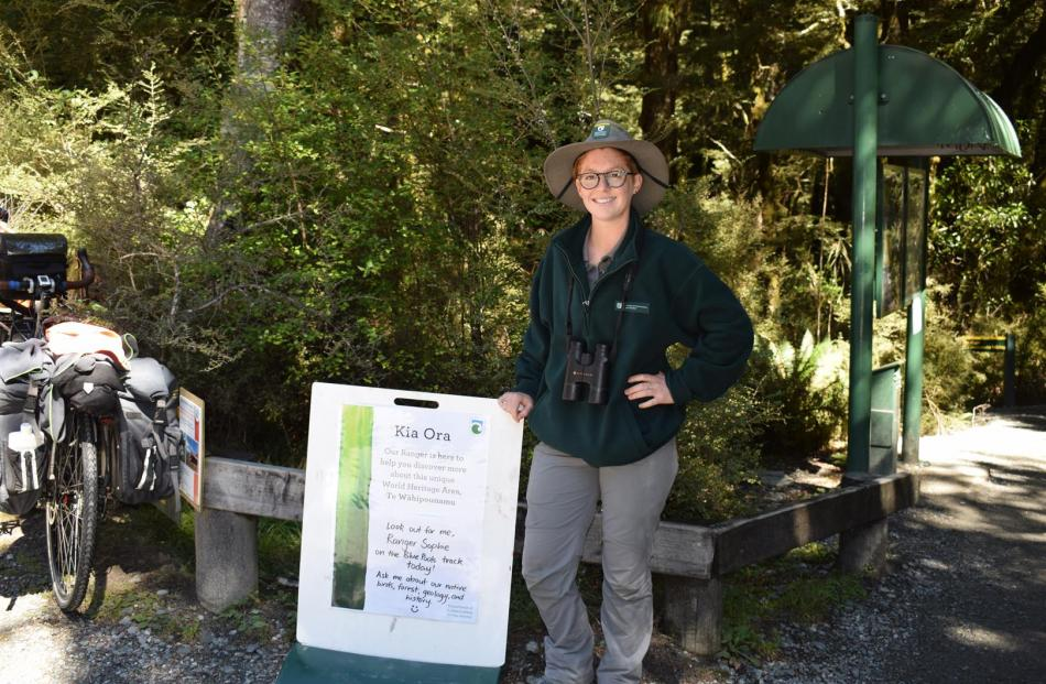 Ranger Sophie Briggs standing beside the Doc notice at the start of the Blue Pools Track alerting walkers there is a ranger on the walk today. Photos: Kerrie Waterworth