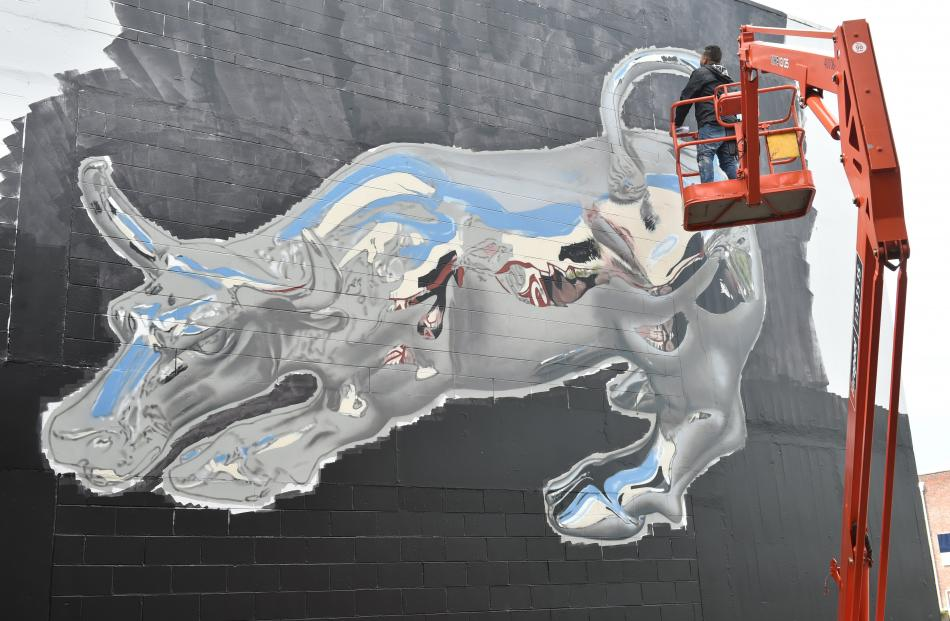 Puerto Rican artist Joshua Santos Rivera works on his 3-D metallic bull in the Dowling St car park.