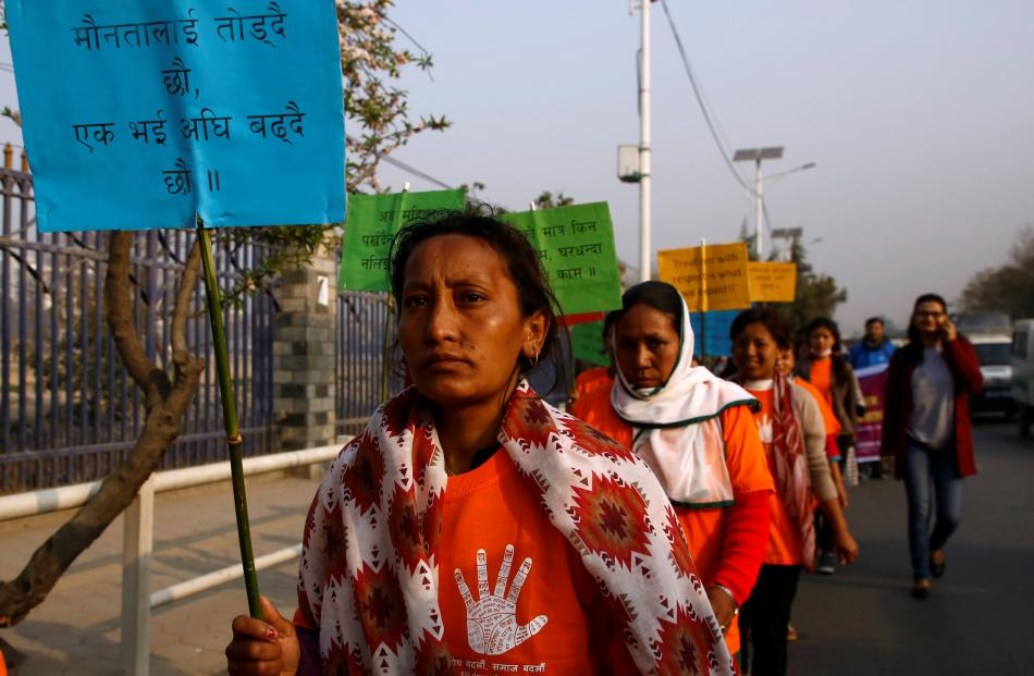"""A Nepalese woman with a placard that says """"We are advancing together and breaking the silence""""..."""