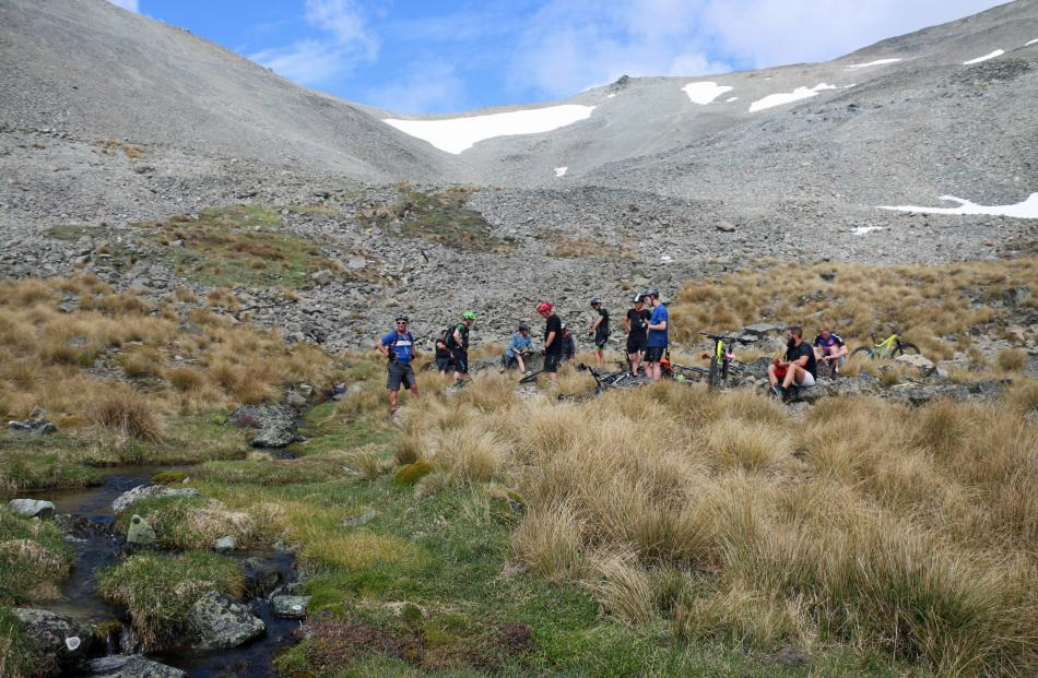 Riders take a break and replenish their supplies in an alpine stream.