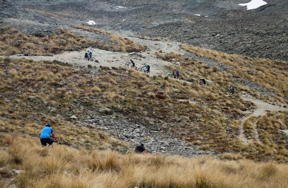 The rough slope forced some riders to push their biker during the ride to the ridgeline above the...