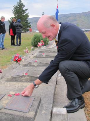 Cromwell RSA president Denis Ryan lays poppies on returned servicemen's graves in Cromwell...