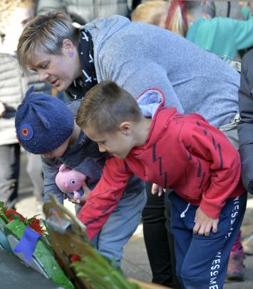 Melissa Hannagan helps sons Max and Isaac lay poppies after yesterday morning's Anzac service in...