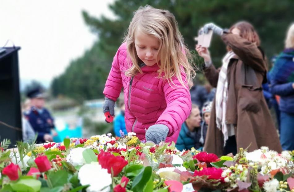 Mikayla Clark (7), of Lake Hawea, lays a poppy on the Hawea Memorial yesterday morning at her...
