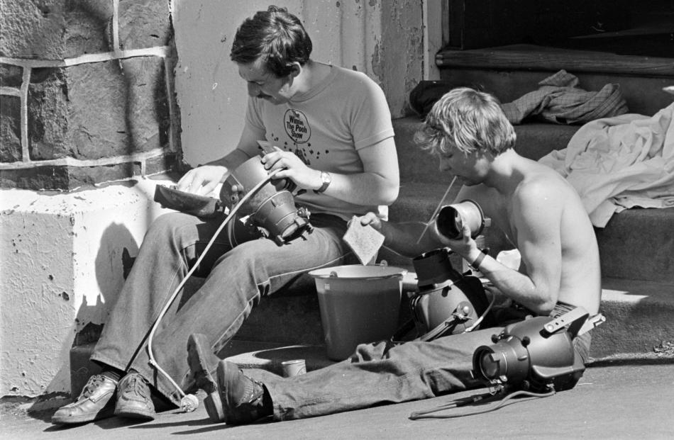 Actors Geoffrey Heath (left) and Simon Marley-Jones clean spotlights damaged by smoke in the 1979...