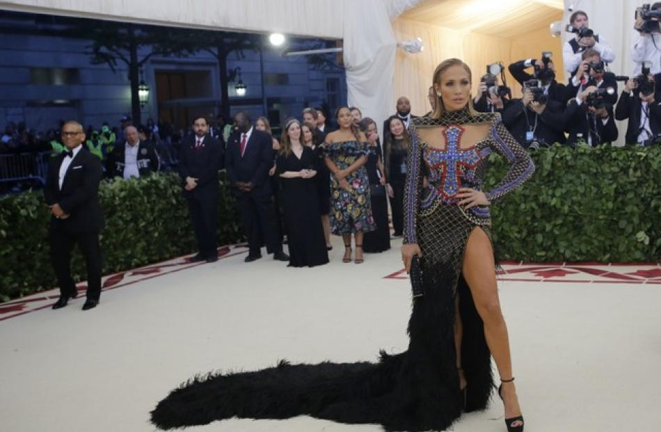 Jennifer Lopez chose a Balmain dress, split to the hip, with a large cross across the breast and a black feathered train. Photo: Reuters