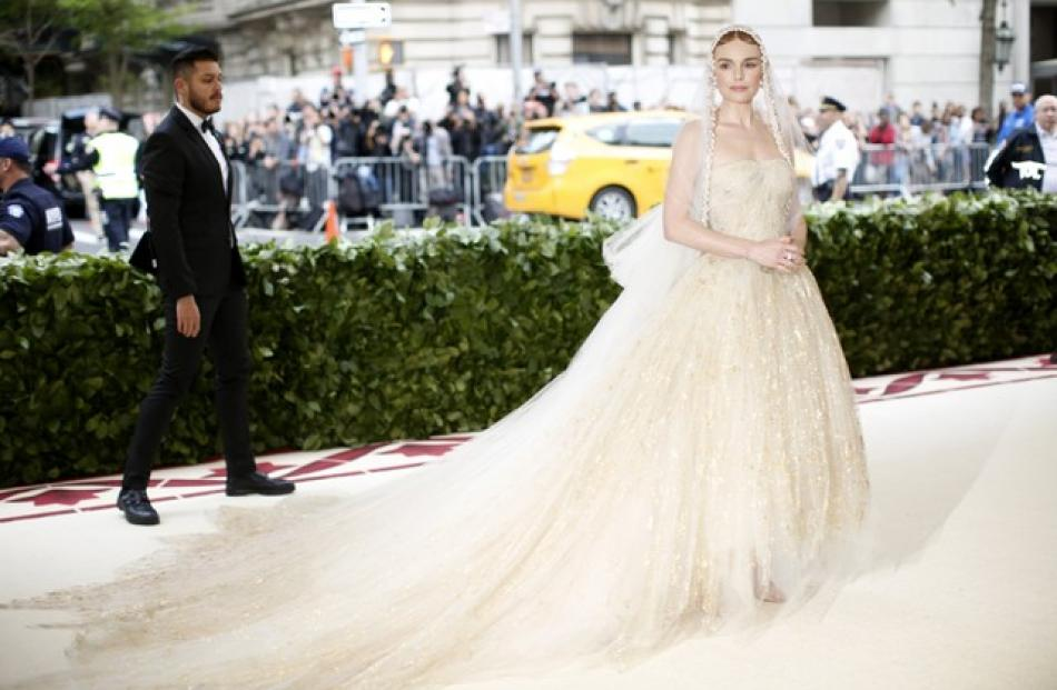 Kate Bosworth looks regal in an off-white gown with a long train. Photo: Reuters