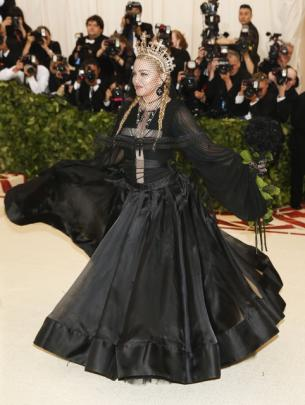 Madonna, a key religious provocateur early in her pop career, turned demure in a black, long-sleeved gown, with a huge gold crown, and a full face veil. Photo: Reuters