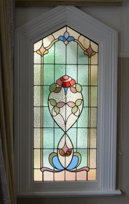 One of two original stained-glass windows that stand either side of the front door.