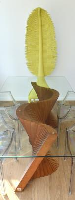 The wooden base for the dining table reflects the waves outside while a lime green chair has a...