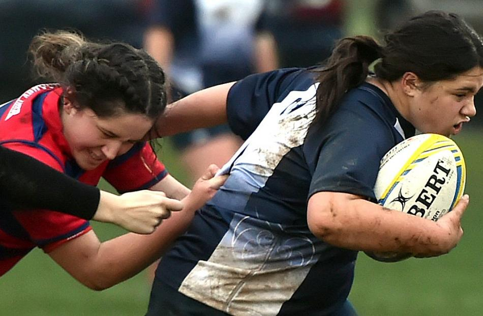 Olivia Fowler (15), of Columba College, gets a pass away as she is tackled by Beryn Abbott (17) of St Hilda's Collegiate