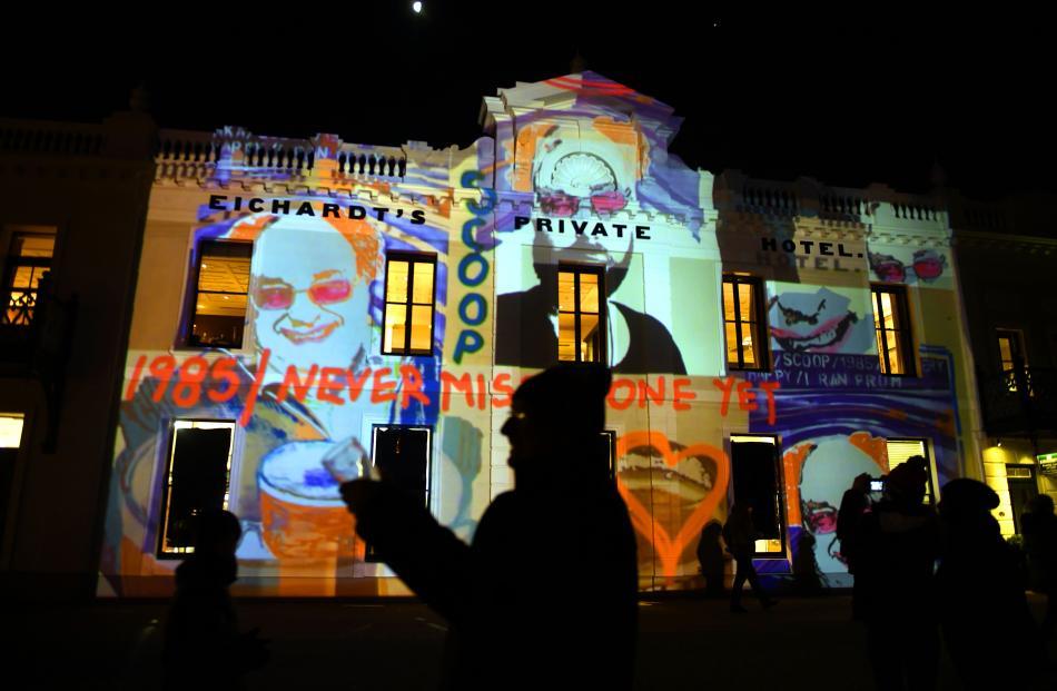 Queenstown media celebrity Scoop (Philip Chandler) stands in front of a surprise projection of...