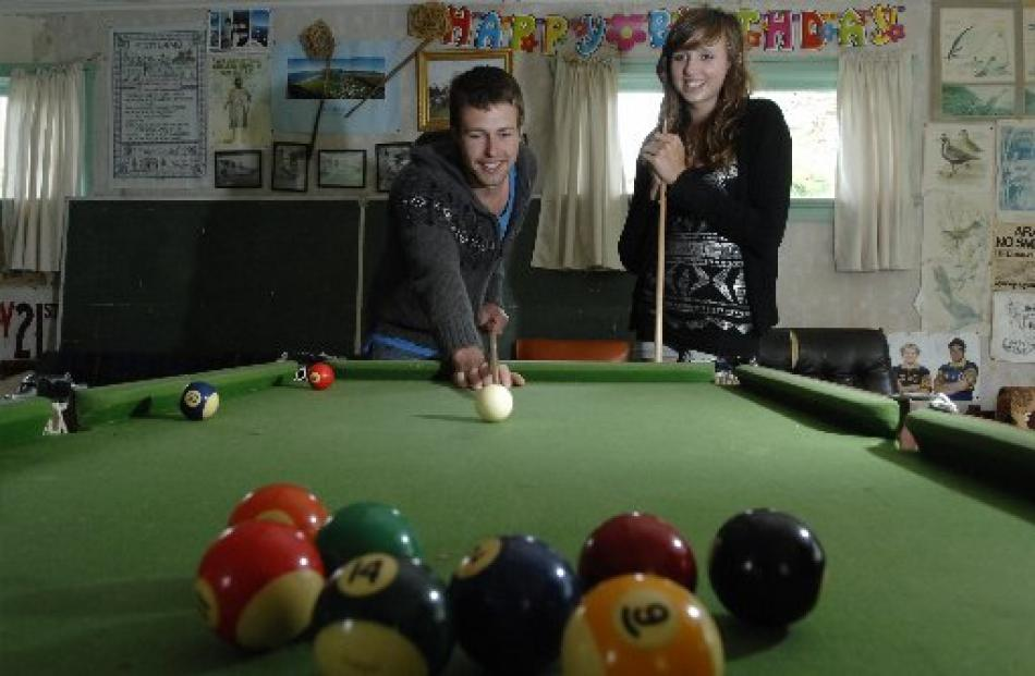 Cousins Louis (23) and Paige (15) Munro, of Dunedin, play pool at the family crib at Aramoana.