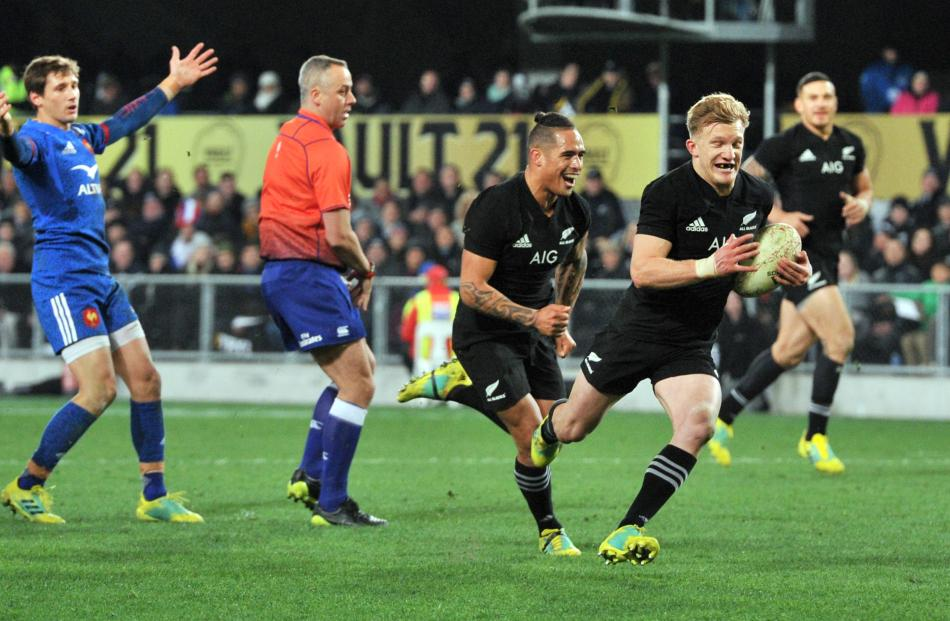 Damian McKenzie scores with the support of halfback Aaron Smith while French halfback Baptiste...