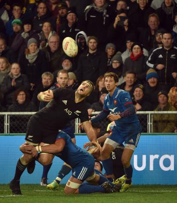 All Black No 8 Luke Whitelock eyes the ball in the tackle of French lock Yoann Maestri while...