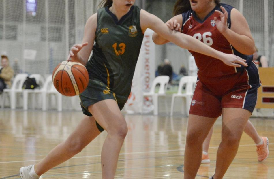 Kashya Arras-Scott  Bayfield High School) brushes past Nadia Uriaro (Kavanagh College) during a...