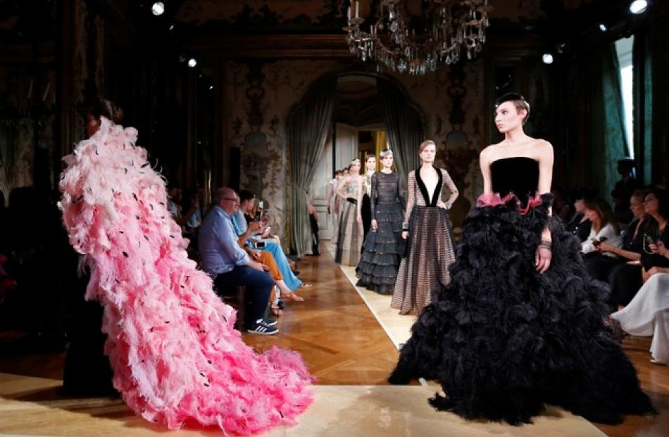 Fringed dresses gave way to enormous puffy skirts swirling in feathers as models wound their way around the rooms of the Italian embassy in Paris. Photo: Reuters
