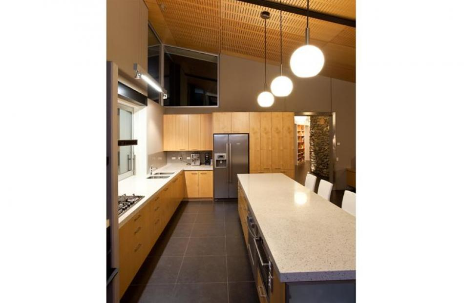 Timber accoustic ceiling panels offset the ceramic floor tiles in the kitchen.