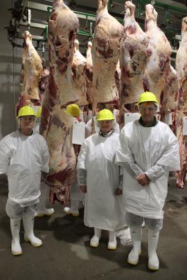 Otago/Southland Beef Carcass Competition on-the-hook judge Neil Willis, left, with winners Evan Ferris and Kay Worthington examining the winning carcass behind them at the Mataura Alliance Plant last week.