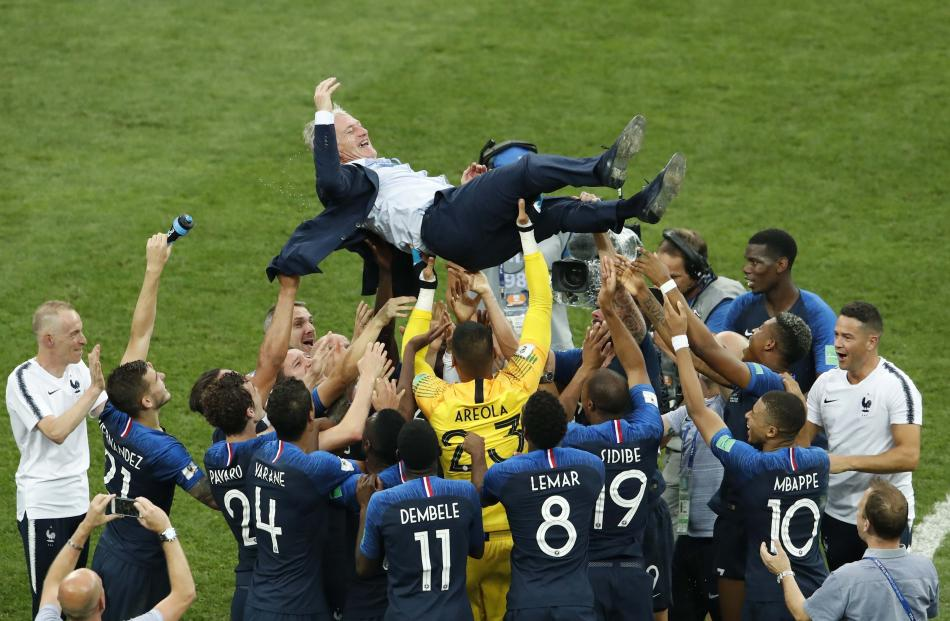 France players celebrate winning the World Cup with coach Didier Deschamps. Photo: Reuters