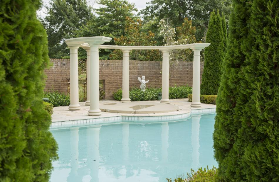An architectural structure graces Jason and Janine's formal poolside garden.