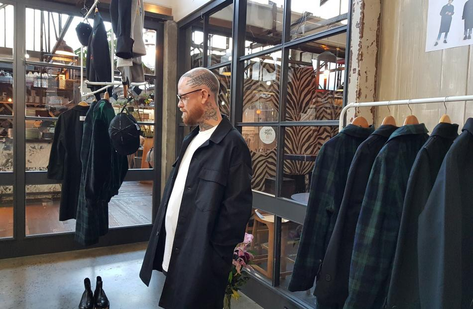 A customer tries on a jacket in Jun's Ponsonby pop-up store