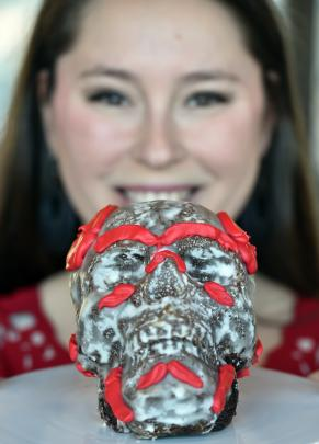 PhD student Jade De La Paz (left) shows off with her cake which tied into her work on estimating biological sex by studying the skull. Photos: Peter McIntosh