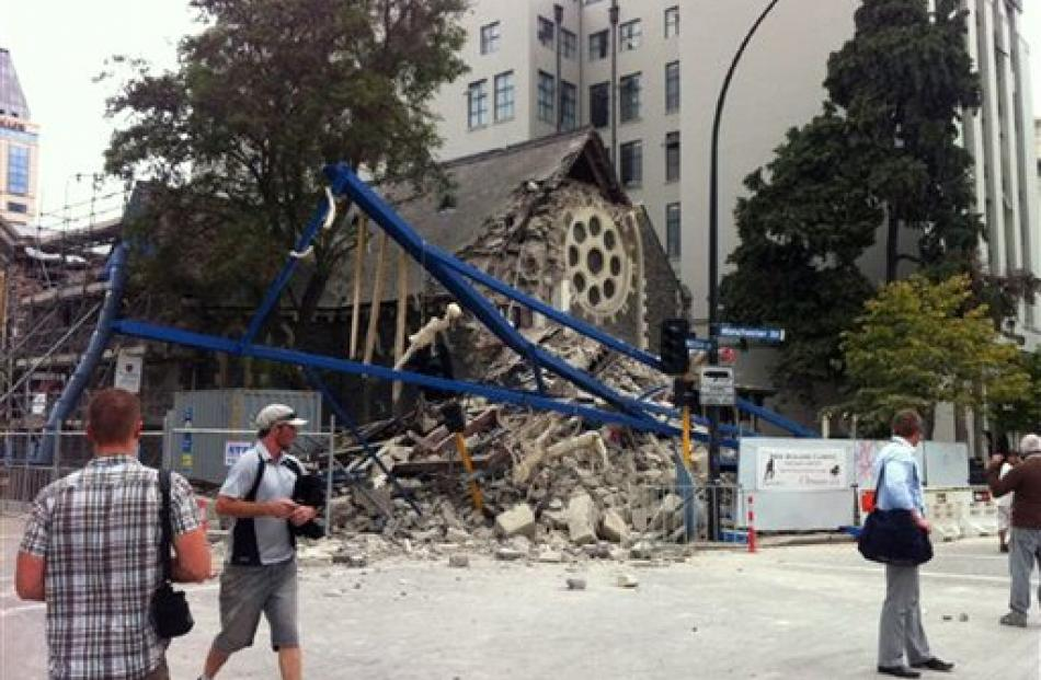 People look at a damaged church after a powerful earthquake struck Christchurch today. Photo by AP.